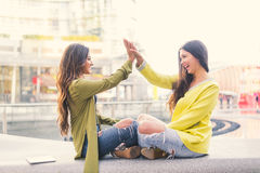 Two women giving high five. Two beautiful young women giving high five - Pretty girls sitting on a bench outdoors and having fun - Best girlfriends making a Royalty Free Stock Photos