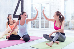 Two women giving high five at gym. Hey sister. Nice attractive girls women are giving high five to each other after doing some stretching at gym Stock Image