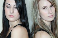 Two women glaring. Two beautiful women standing back to back while glaring Royalty Free Stock Image