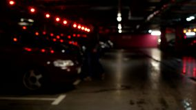 Two women go and sit in their car in the underground parking lot, blurred. Shopping stock footage