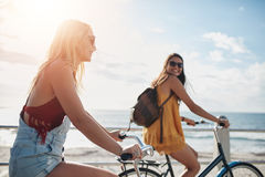 Two women going by bike on sunny day. Two female friends riding cycles on the seaside promenade. Happy young women enjoying riding bicycles on a summer day stock images