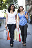 Two women going shopping. Two female friends on the sidewalk in the city shopping Stock Photos