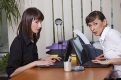 Two women gossip in office. Two women in office looking at someone Stock Images