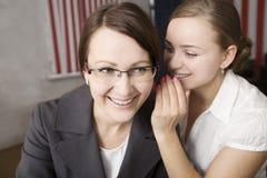 Two women gossip at work Stock Photos