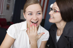 Two women gossip at work Royalty Free Stock Photo