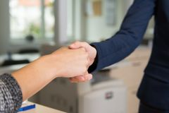 Two women greet each other. With handshake in the office royalty free stock images