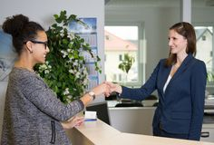 Two women greet each other. Two smiling women greet each other with handshake over a counter in the office stock image