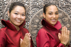 Two women greeting. Two young women dressed in red silk dresses greeting Stock Photo