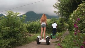 Two women and guide on segway tour in hills, cloudy