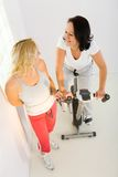 Two women at gym. Two women dressed sportswear. One of them exercising on spinning bike. High angle view Royalty Free Stock Photo