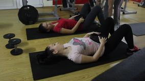 Two women at the gym. Exercises to strengthen abdominal muscles stock video
