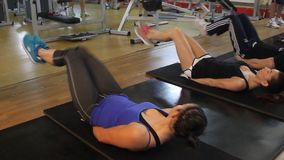 Two women at the gym. Exercises to strengthen abdominal muscles stock video footage
