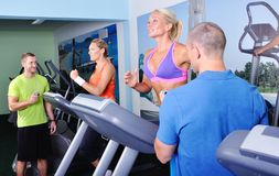 Two women in gym exercising with personal fitness trainer. Two women exercising with personal fitness trainer Royalty Free Stock Photos