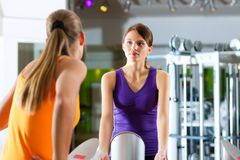 Two women in gym in front of a exercising machine. Having a chat Royalty Free Stock Photo