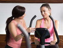 Two women gym instructor talking listening bike sitting standing Stock Photos