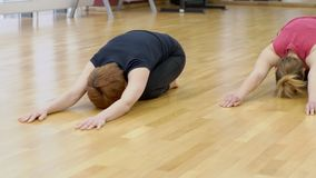 Two women in the gym make an asana posture of a baby on the floor. In group, people synchronously make a balasan during a Pilates training session stock footage