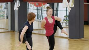 Two women in gym make complex gymnastic exercises standing on one leg. Adult and young female athletes perform a difficult acrobatic element during training stock video