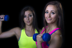 Two women in the gym. Portrait of two attractive smiling young women in the gym both holding blue weights, dark background Stock Images