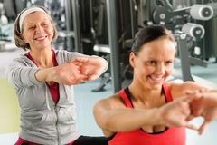 Two women at gym stretch out Royalty Free Stock Images