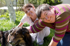 Two women and a half breed dog. On a field Stock Image