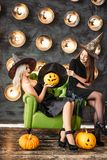 Two women in halloween costumes on party sitting on chair over bulb background. Two happy young women in black witch halloween costumes on party sitting on chair Royalty Free Stock Photos