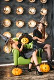Two women in halloween costumes on party sitting on chair over bulb background. Two happy young women in black witch halloween costumes on party sitting on chair Royalty Free Stock Images