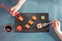 Two women hands with chopsticks and fork. Royalty Free Stock Photo