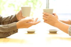 Two women hands talking in a bar holding coffee cups. Side view close up of two women hands talking in a bar or house holding coffee cups Royalty Free Stock Image