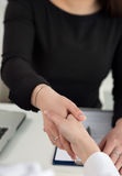 Two women handshake in office closeup. Businesswomen shaking hands. Serious business, partnership and collaboration concept. Partners made deal and sealed it Royalty Free Stock Images