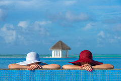 Two women in a hat sitting on the edge of the swimming pool Royalty Free Stock Images