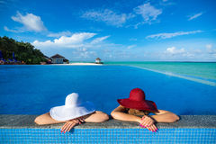 Two women in a hat sitting on the edge of the swimming pool Royalty Free Stock Photo