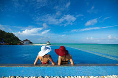Two women in a hat sitting on the edge of the swimming pool.  stock images