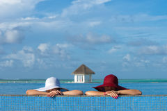 Two women in a hat sitting on the edge of the swimming pool.  royalty free stock photos