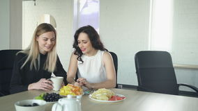 Two women have coffee break, discuss manicure indoor. Attractive woman with red full lips, dark curly long hair in white transparent top with gold chain as stock footage