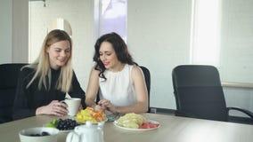 Two women have coffee break, discuss manicure indoor. stock footage