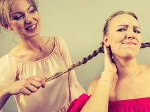 Two women having argue fight. Two young pretty women being mad at each other having argue fight pulling hair. Friendship rivaly and envy problems Royalty Free Stock Photography