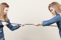Two women having argue pulling rope. Being mad at each other. Bad rivalry relationship Stock Photos