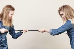 Two women having argue pulling rope. Being mad at each other. Bad rivalry relationship Stock Image