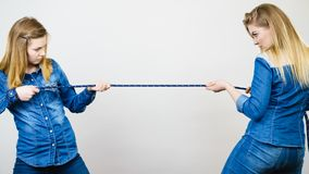 Two women having argue pulling rope. Being mad at each other. Bad rivalry relationship Stock Images