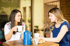 Two women having coffee at cafe. Two young women enjoying some coffee together in a restaurant and talking stock photography