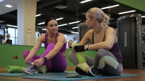 Two women are having fun during a break to workout on floor in gym. After hard workout, beautiful female friends share their impressions about exercises and stock footage