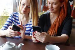 Two women having fun at the cafe and looking at smart phone. Stock Image