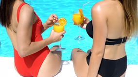 Two women having fun at poolside with fresh cocktails, summer vacation, holiday. Stock photo stock images