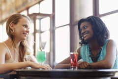 Two women having fun in pub. African and latin american female friends drinking cocktails and talking in a pub. Horizontal shape, side view, waist up Stock Photography