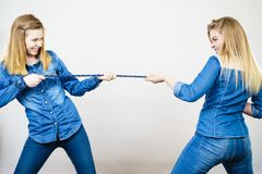 Two women having fun pulling rope. Two women wearing jeans outfit having fun pulling rope, good rivalry concept. Sporty competition Royalty Free Stock Photo