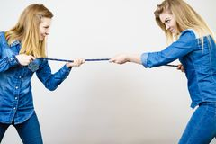 Two women having fun pulling rope. Two women wearing jeans outfit having fun pulling rope, good rivalry concept. Sporty competition Royalty Free Stock Image