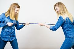 Two women having fun pulling rope. Two women wearing jeans outfit having fun pulling rope, good rivalry concept. Sporty competition Stock Photo