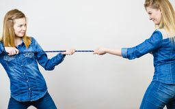 Two women having fun pulling rope. Two women wearing jeans outfit having fun pulling rope, good rivalry concept. Sporty competition Royalty Free Stock Photography