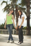 Two women having fun under palm trees Stock Photo
