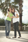 Two women having fun under palm trees Royalty Free Stock Image
